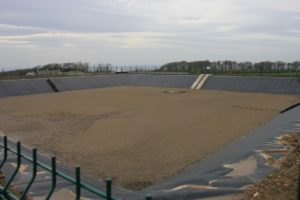 Earth banked and sheet lined slurry lagoon part filled with slurry